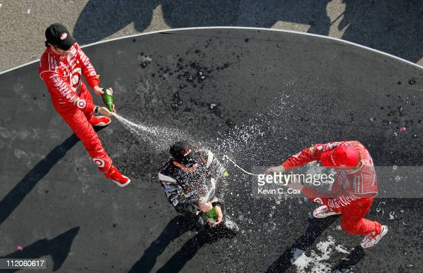 Will Power of Australia driver of the Team Penske Dallara Hondais doused with champagne by Scott Dixon of New Zealand driver of the Target Chip...
