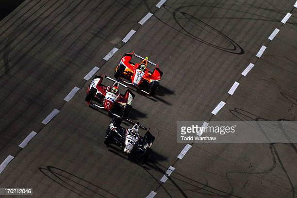 Will Power of Australia driver of the Verizon Team Penske Chevrolet races Justin Wilson of England driver of the Dale Coyne Racing Honda and EJ Viso...