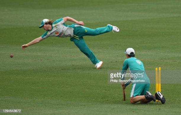 Will Pucovski of Australia dives for a catch watched by Justin Langer during an Australian training session before the third Test match against India...