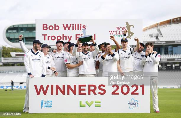 Will Rhodes of Warwickshire lifts the Bob Willis Trophy with his teammates after victory on Day 4 of the Bob Willis Trophy Final between Warwickshire...