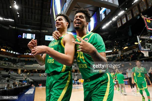 Will Richardson and Aaron Estrada of the Oregon Ducks leave the court after defeating the Iowa Hawkeyes in the second round game of the 2021 NCAA...