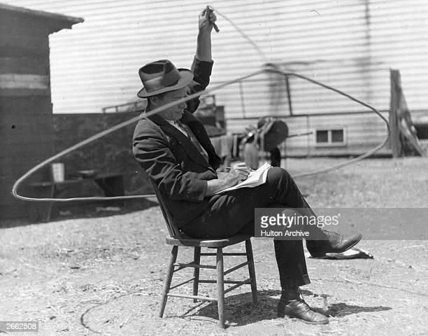 Will Rogers American rustic comedian playing with a lasso whilst writing himself some notes Original Publication People Disc HK0481
