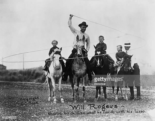 Will Rogers rides a horse and swings a lasso while a man and three children stand next to him on or near horses Rogers was a well known American...