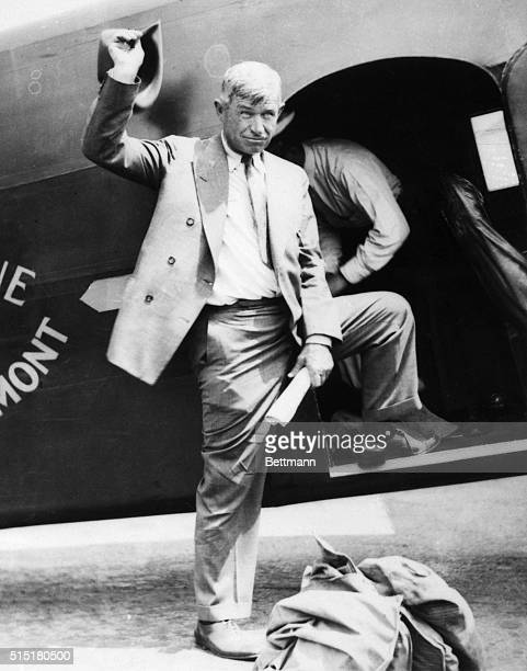 Will Rogers standing next to an airplane Waves his hat Undated photograph