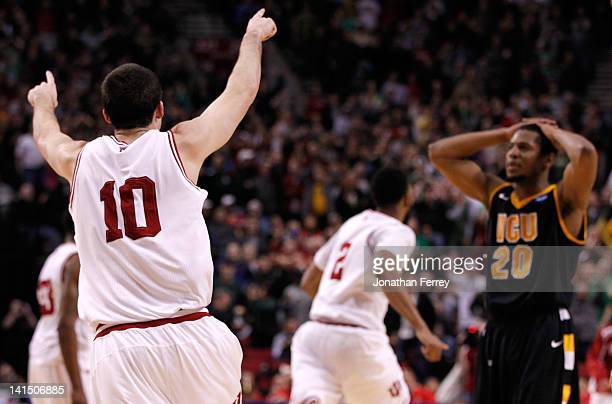 Will Sheehey and Christian Watford of the Indiana Hoosiers celebrates as Bradford Burgess of the Virginia Commonwealth Rams reacts after losing to...