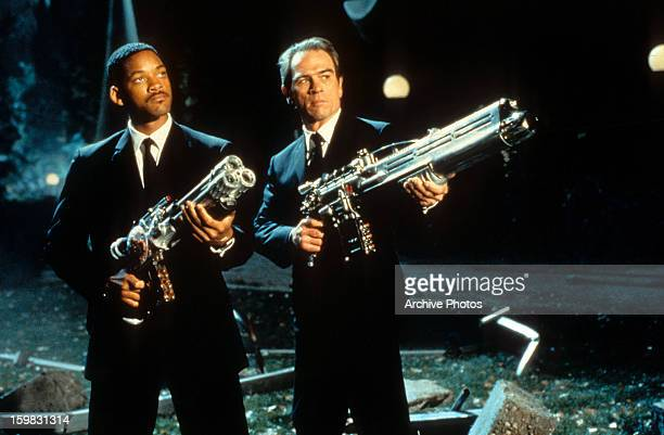 Will Smith and Tommy Lee Jones aiming their weapons towards the sky in a scene from the film 'Men In Black' 1997