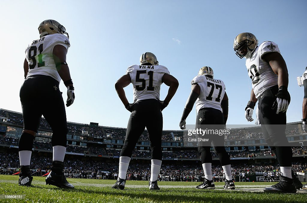 Will Smith #91, Jonathan Vilma #51, Brodrick Bunkley #77, and Curtis Lofton #50 of the New Orleans Saints stand on the sidelines during their game against the Oakland Raiders at O.co Coliseum on November 18, 2012 in Oakland, California.