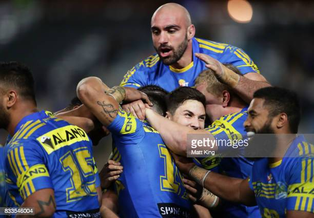 Will Smith of the Eels celebrates with team mates after scoring the final try as Tim Mannah of the Eels jumps over the top during the round 24 NRL...