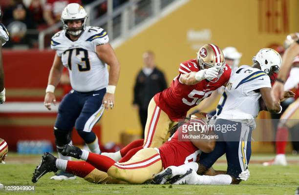 Will Sutton and Brock Coyle of the San Francisco 49ers sack Geno Smith of the Los Angeles Chargers during the game at Levi Stadium on August 30, 2018...
