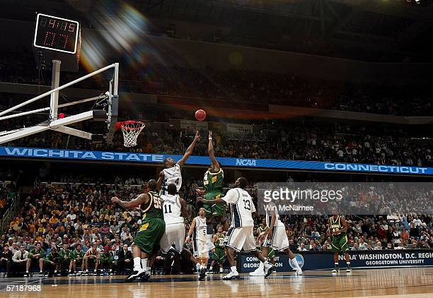 Will Thomas of the George Mason Patriots puts up a shot over Jeff Adrien of the Connecticut Huskies during the Regional Finals of the NCAA Men's...