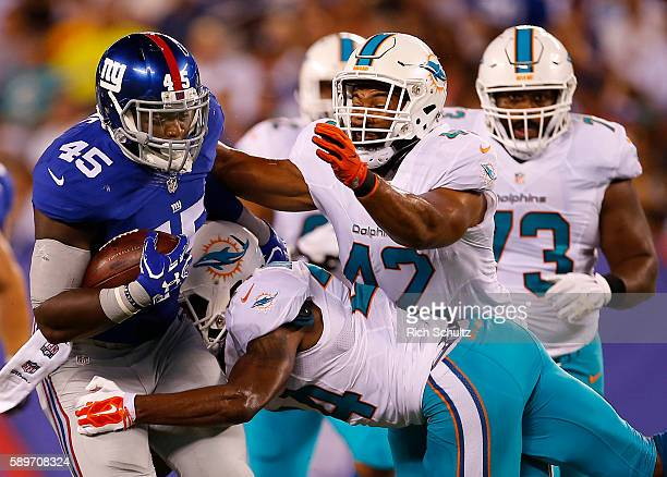 Will Tye of the New York Giants of the New York Giants runs and is tackled by Isa AbdulQuddus and Spencer Paysinger of the Miami Dolphins during the...