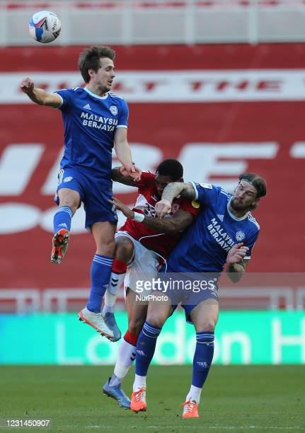 Will Vaulks and Aden Flint of Cardiff City contests a header with Middlesbrough's Britt Assombalonga during the Sky Bet Championship match between...