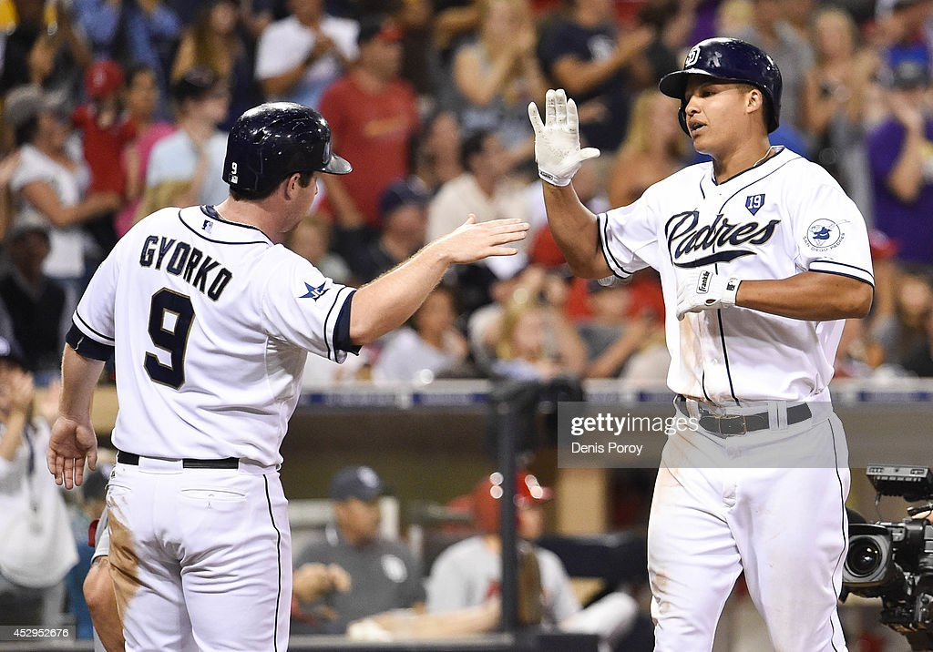 Will Venable #25 of the San Diego Padres, right, is congratulated by Jedd Gyorko #9 after hitting a three-run home run during the seventh inning of a baseball game against the St. Louis Cardinals at Petco Park July 30, 2014 in San Diego, California.