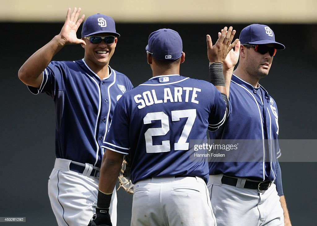 Will Venable #25, Yangervis Solarte #27 and Seth Smith #12 of the San Diego Padres celebrate winning the game against the Minnesota Twins on August 6, 2014 at Target Field in Minneapolis, Minnesota. The Padres defeated the Twins 5-4 in ten innings.