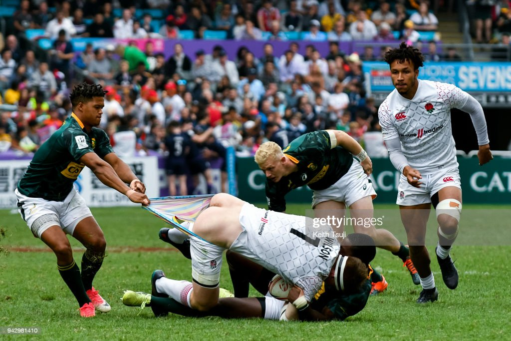 Will Wilson (C) of England is tackled and has his shorts pulled during their match against South Africa on the second day of the Hong Kong Sevens on April 7, 2018 in Hong Kong.