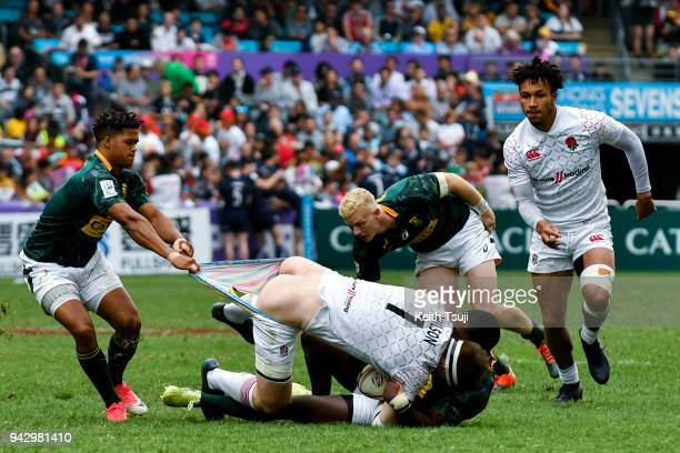 Will Wilson of England is tackled and has his shorts pulled during their match against South Africa on the second day of the Hong Kong Sevens on...