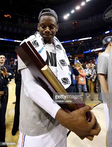 Will Yeguete of the Florida Gators celebrates with the trophy on the court after defeating the Dayton Flyers 6252 in the south regional final of the...