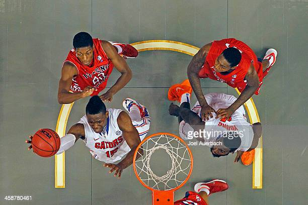 Will Yeguete of the Florida Gators goes to the basket past Paul Watson of the Fresno State Bulldogs during the MetroPCS Orange Bowl Basketball...