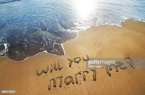 Will you marry me written in sand on beach