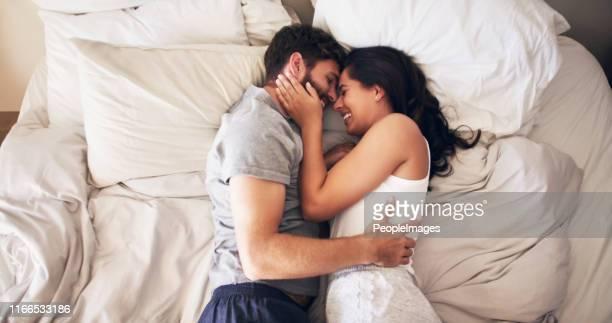¿te quedarás en mi corazón para siempre? - pareja abrazados cama fotografías e imágenes de stock