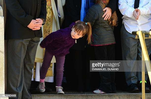 Willa the youngest daughter of late actor Philip Seymour Hoffman looks as her dad's casket is loaded onto a hearse following his funeral at St...