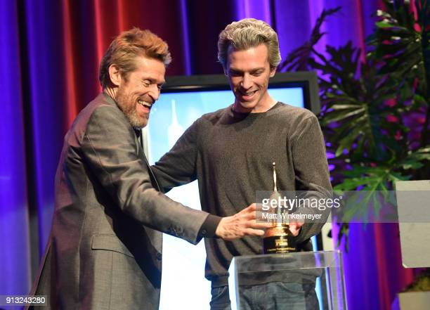 Willem Dafoe accepts the Cinema Vanguard award from director Josh Boone onstage at the Cinema Vanguard Award Honoring Willem Dafoe during The 33rd...