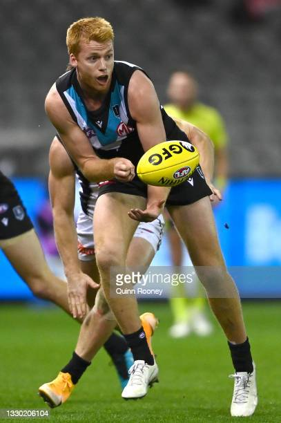 Willem Drew of the Power handballs whilst being tackled during the round 19 AFL match between Port Adelaide Power and Collingwood Magpies at Marvel...