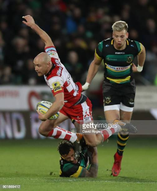 Willi Heinz of Gloucester is tackled by Courtney Lawes and Harry Mallinder during the Aviva Premiership match between Northampton Saints and...