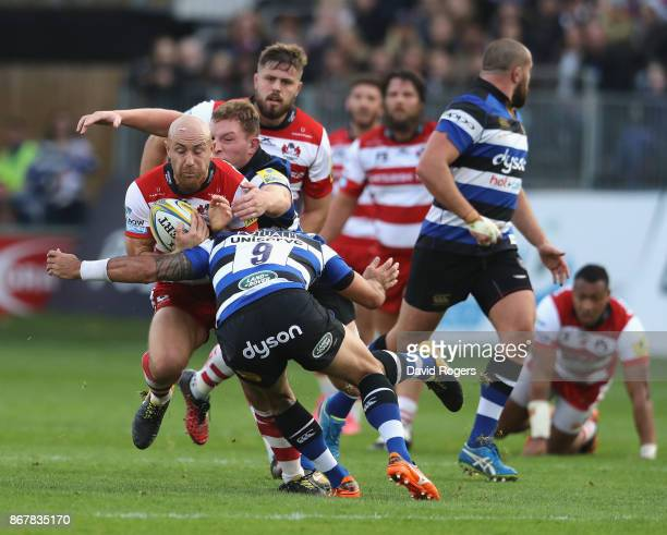 Willi Heinz of Gloucester is tackled by Sam Underhill and Kahn Fotuali'i during the Aviva Premiership match between Bath Rugby and Gloucester Rugby...