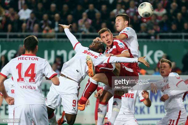 Willi Orban of Kaiserslautern jumps for a header with Anthony Ujah and Kevin Wimmer of Koeln during the Second Bundesliga match between 1 FC...