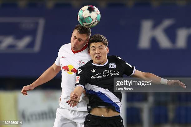 Willi Orban of Leipzig battles for the ball with Ritsu Doan of Bielefeld during the Bundesliga match between DSC Arminia Bielefeld and RB Leipzig at...