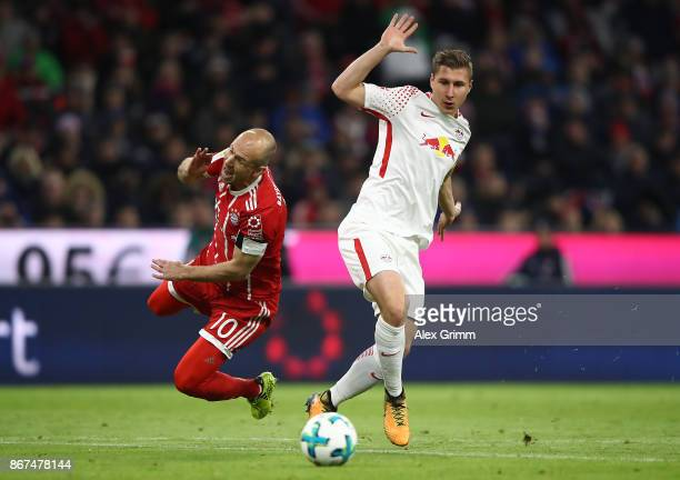 Willi Orban of Leipzig fouls Arjen Robben of Bayern Muenchen which later results in a red card for Orban during the Bundesliga match between FC...