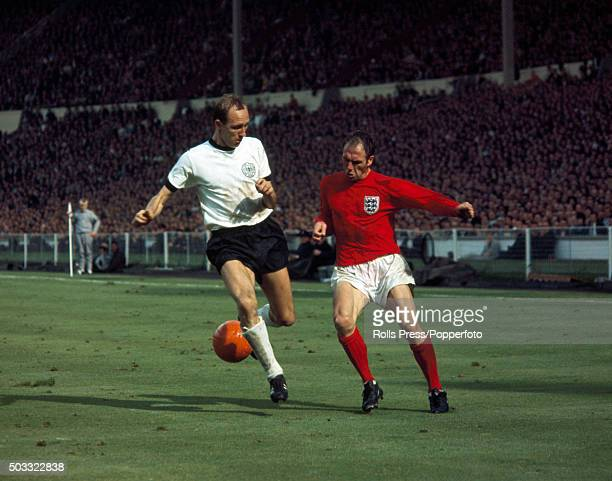 Willi Schulz of West Germany clashes with England fullback Ray Wilson during the FIFA World Cup Final between England and West Germany at Wembley...