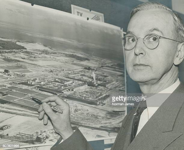 William A Wecker General Motors of Canada president points to an aerial photo of the new Oshawa plant which will step up production to 1350 vehicles...