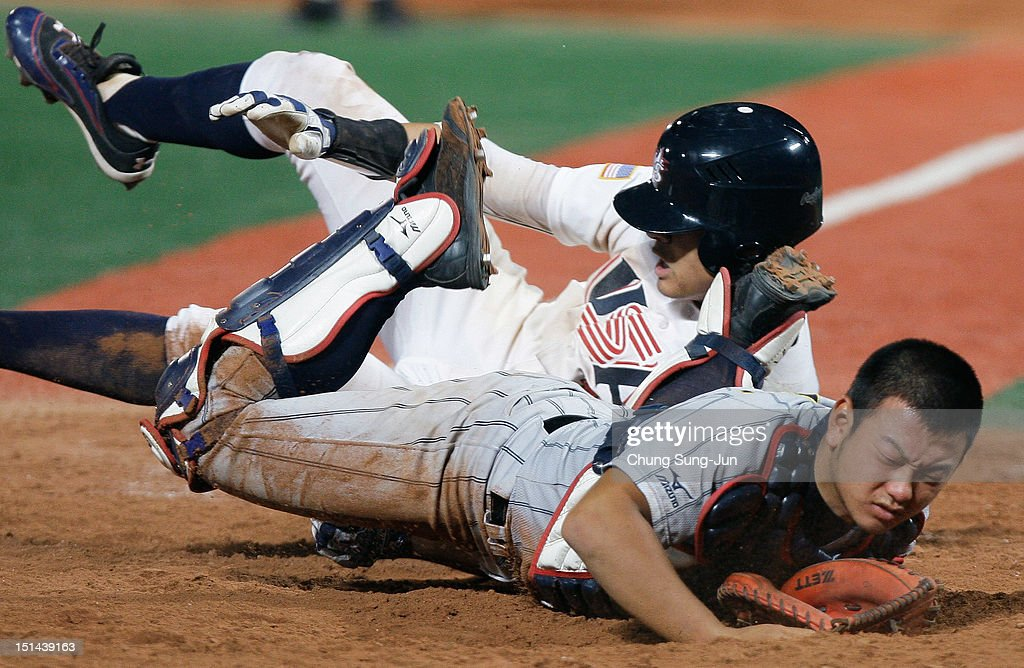 William Abreu of United States slides safely into home and scores a run past catcher Tomoya Mori of Japan in the seventh inning during the U18 Baseball World Championship match between Japan and the United States at Mokdong Stadium on September 7, 2012 in Seoul, South Korea.