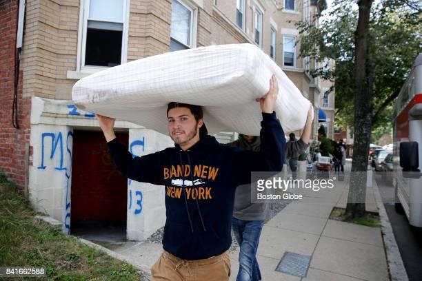 William Anderson front and his fellow Boston University student Edward Harris rear walk down Pratt Street in the Allston neighborhood of Boston with...