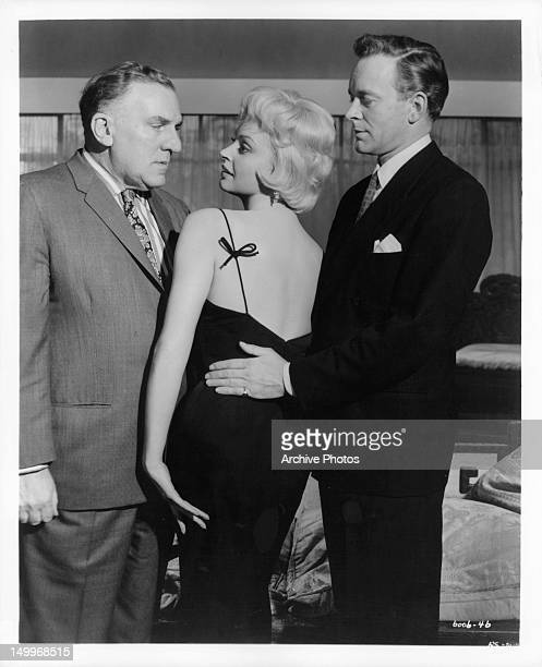 William Bendix looking into the eyes of Nadja Tiller with Tony Britton behind her in a scene from the film 'Portrait Of A Sinner' 1960