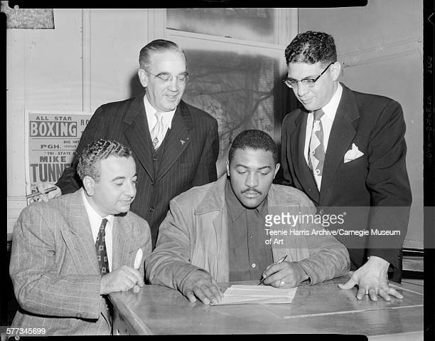 William Bettor TW Stephen and Anthony 'Cowboy' DeLuca surrounding boxer Bob Baker signing contract in office Pittsburgh Pennsylvania October 1952
