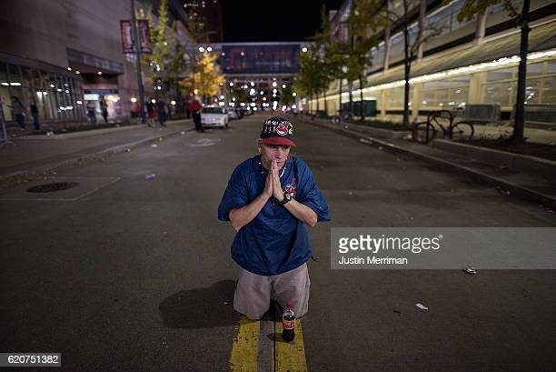 William Burgos of Cleveland prays in the street outside of Progressive Field during the 9th inning of game 7 of the World Series between the...