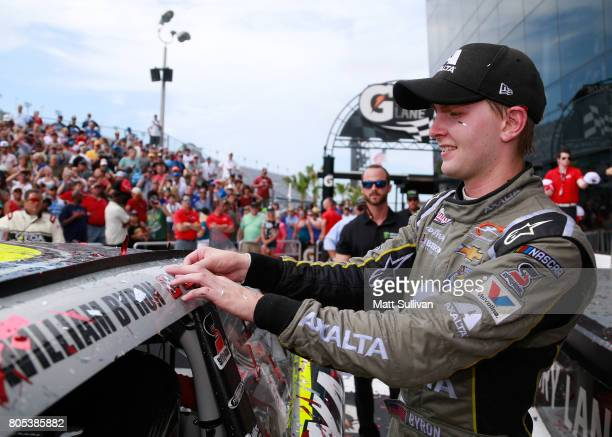 William Byron driver of the AXALTA/Vorteq Chevrolet affixes the winner's decal to his car in Victory Lane after winning the NASCAR XFINITY Series...
