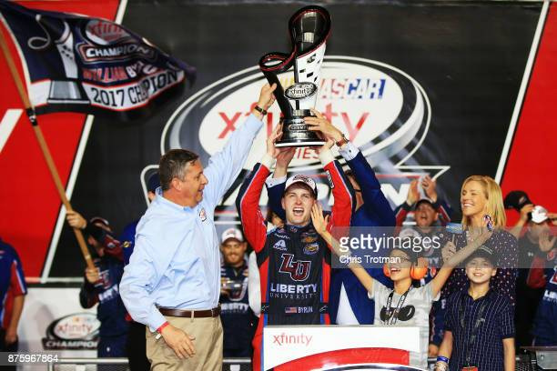 William Byron driver of the Liberty University Chevrolet celebrates with the trophy in Victory Lane after placing third and winning the NASCAR...
