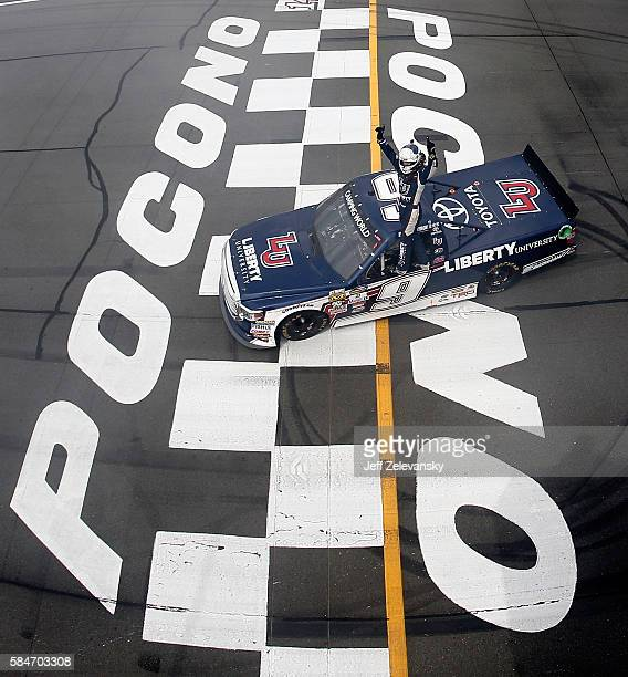 William Byron driver of the Liberty University Toyota celebrates after winning the NASCAR Camping World Truck Series Pocono Mountains 150 at Pocono...