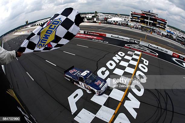 William Byron driver of the Liberty University Toyota takes the checkered flag to win the NASCAR Camping World Truck Series Pocono Mountains 150 at...