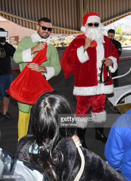 William Carrier of the Vegas Golden Knights dressed as an elf and Ryan Reaves of the Golden Knights dressed as Santa Claus give out gifts to kids at...