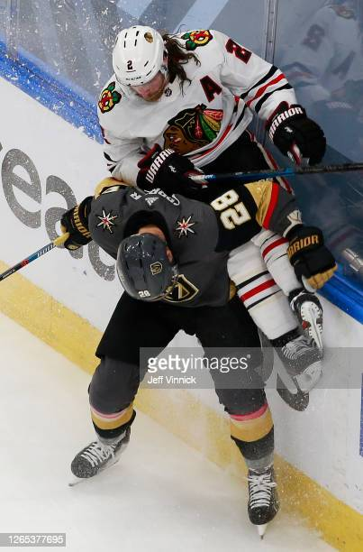 William Carrier of the Vegas Golden Knights checks Duncan Keith of the Chicago Blackhawks into the boards during the second period in Game One of the...
