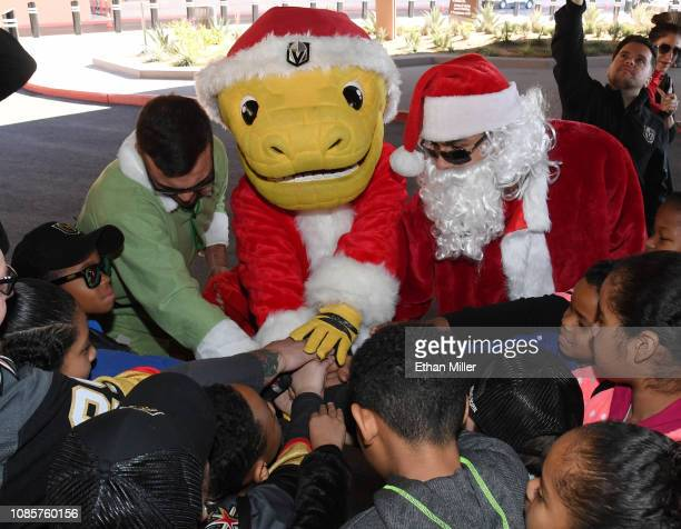 William Carrier of the Vegas Golden Knights dressed as an elf the Golden Knights mascot Chance the Golden Gila Monster and Ryan Reaves of the Golden...
