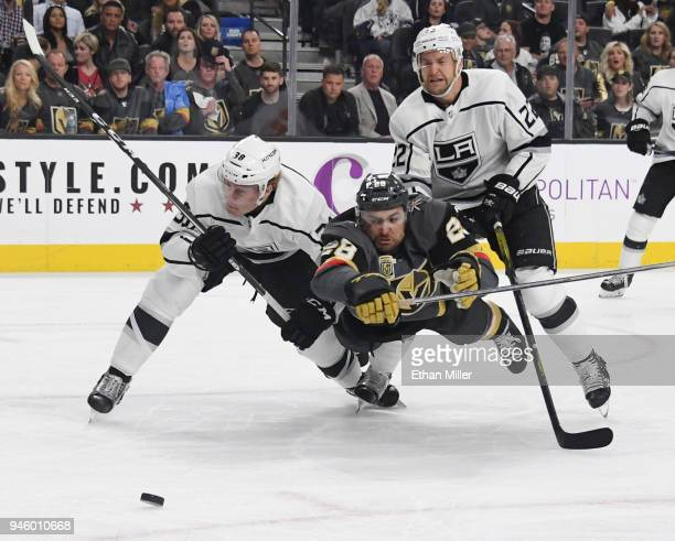 William Carrier of the Vegas Golden Knights tries to stay with the puck as he gets knocked down by Paul LaDue and Trevor Lewis of the Los Angeles...