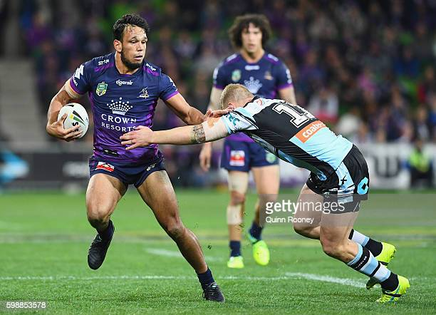 William Chambers of the Storm breaks through a tackle by Luke Lewis of the Sharks during the round 26 NRL match between the Melbourne Storm and the...
