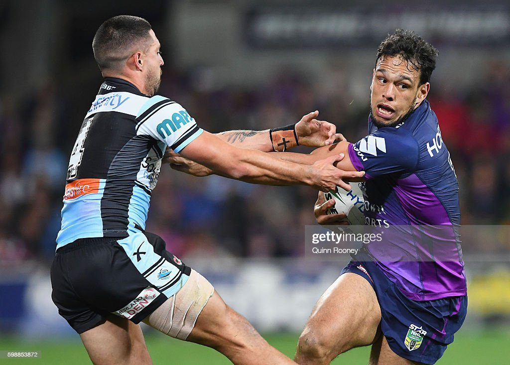 William Chambers of the Storm fends off a tackle by Gerard Beale of the Sharks during the round 26 NRL match between the Melbourne Storm and the Cronulla Sharks at AAMI Park on September 3, 2016 in Melbourne, Australia.