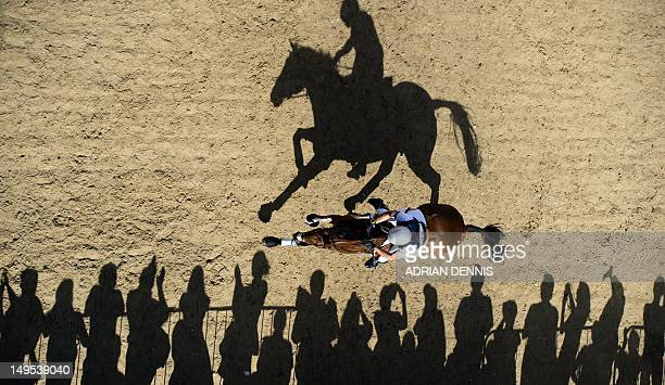 William Coleman of the US riding Twizzel rides past spectators as he competes in the Cross Country phase of the Eventing competition of the 2012...